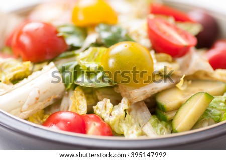 a fresh bowl of salad greens with a healthy vinaigrette dressing, cucumber and tomatoes.
