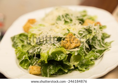 A fresh caesar salad topped with parmesan cheese and croutons