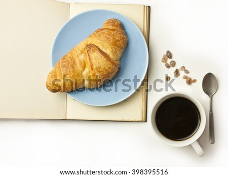 A fresh croissant on a plate on an open old book with a blank page for copyspace, with a cup of black coffee, some cane sugar, and a small spoon, shot on white background from above - stock photo