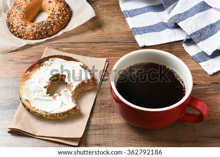 A fresh cup of coffee and a bagel with cream cheese on a wood table.  - stock photo