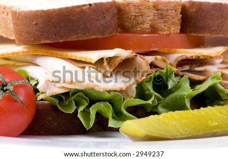 A fresh deli sandwich with tomatoes cheese, lettuce and lots of turkey meat.