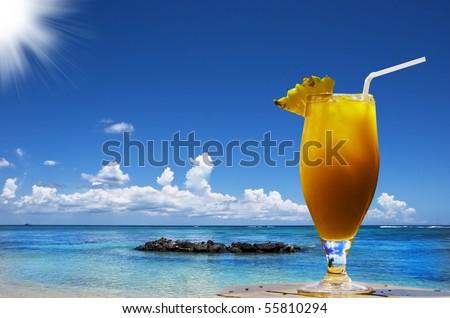 a Fresh fruit cocktail on a tropical island beach - stock photo