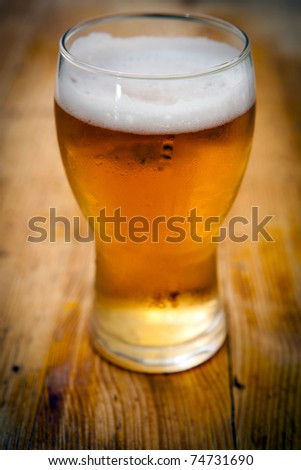 a fresh glass of beer on wooden background - stock photo