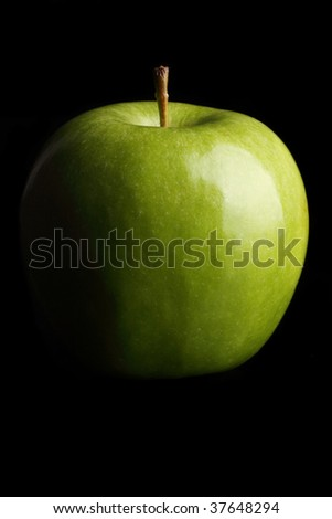 A fresh Granny Smith apple on a black background.