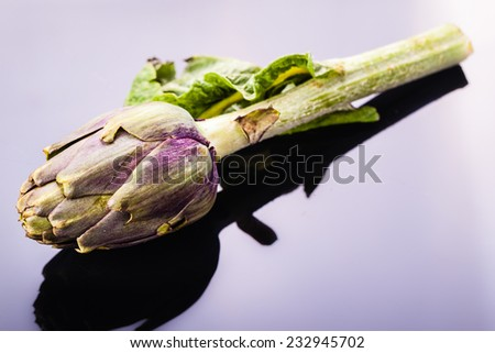 a fresh green artichoke over a sleek reflective black surface - stock photo
