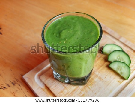 A fresh, green blended smoothie drink on a small cutting board with cucumber slices. - stock photo