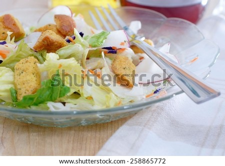 A fresh, green salad in a cut glass bowl with a fork. Includes green lettuce, white and red radishes, purple cabbage, grated orange carrots and croutons. Oil and vinegar are visible in the background - stock photo