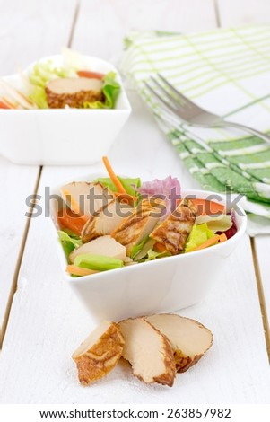 A fresh mixed salad appetizer with grilled chicken slices in a heart shaped bowl - stock photo