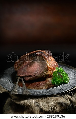 A fresh oven roasted joint of silverside beef in a rustic setting with classic lighting accentuating the quality of the food. A perfect image for a restaurant Sunday lunch design. Generous copy space. - stock photo