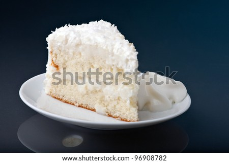 A fresh piece of coconut cream cake on a white plate with a bit of whipped cream on the side. - stock photo