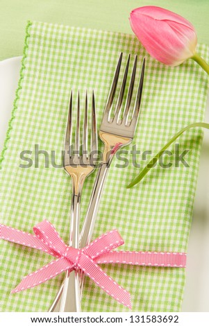 A fresh Spring place setting shows two forks on a green checkered napkin decorated with a pink bow and tulip. - stock photo