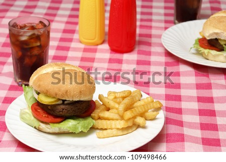 A freshly cooked hamburger and fries meal on a checkered tablecloth.