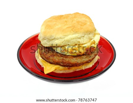 A freshly made sausage egg and cheese breakfast sandwich on a red plate. - stock photo