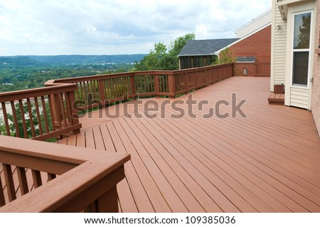A freshly painted and stained wood deck with railing on a summer afternoon.  The deck overlooks a beautiful valley and mountains in the distance.