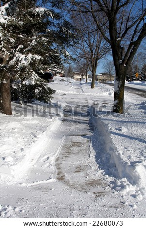 A freshly shoveled sidewalk after a winter snow fall. - stock photo