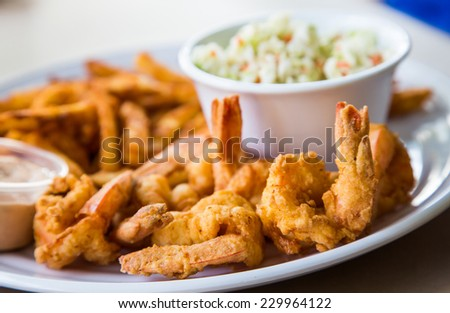 A fried shrimp dinner with french fries, coleslaw and sauce - stock photo