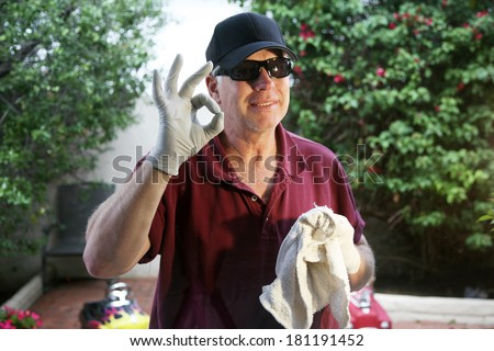 A friendly and professional a window washer soaps and cleans a window with a squeegee, leaving them Squeaky Clean. Everyone Loves Clean Windows especially in the Spring and Summer Season.  - stock photo