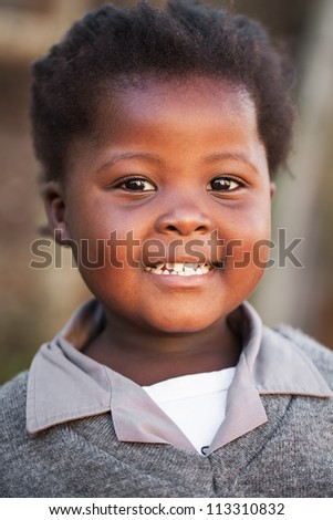 A friendly face is greeting the photographer in the street after school. - stock photo