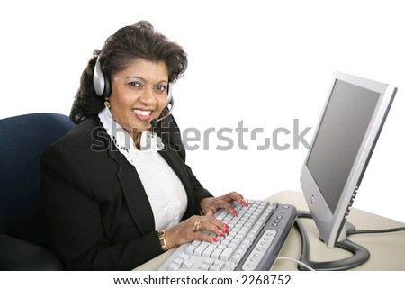 A friendly Indian woman at the computer offering technical support.  Isolated on white. - stock photo