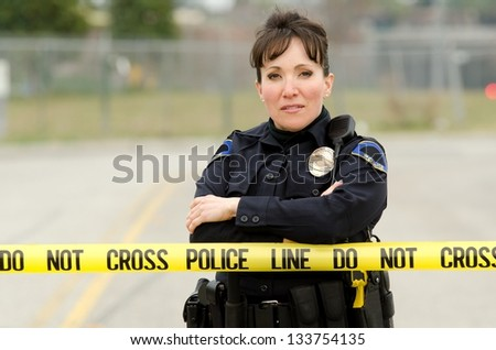 A friendly looking female officer standing behind crime scene tape with her arms crossed.