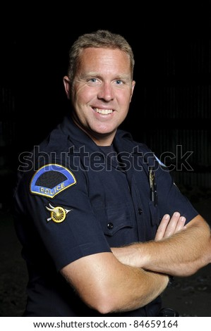 A friendly looking police officer standing with his arms crossed in the night. - stock photo