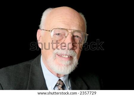 A friendly senior man against a black background. - stock photo