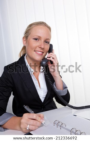 a friendly woman on the phone at her desk in the office and recorded dates in the calendar - stock photo