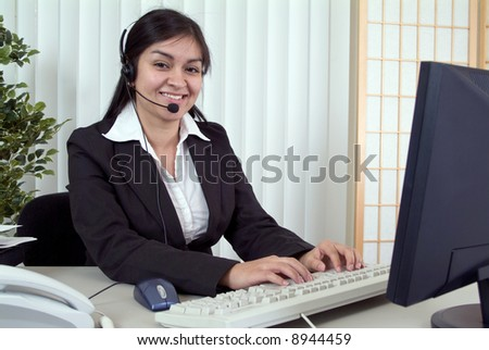 A friendly young woman working at her computer wearing a headset. - stock photo