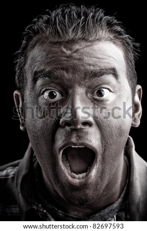 A frightened man with dark skin has a shocked or surprised look on his face. - stock photo