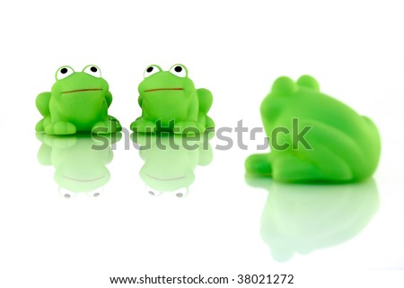A frog couple with a lone onlooker. Isolated on white and shot on glass for reflections and to enhance the scene. - stock photo
