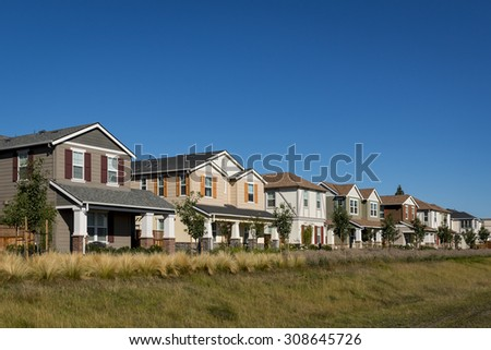 A front corner view of a row of colorful new houses. - stock photo
