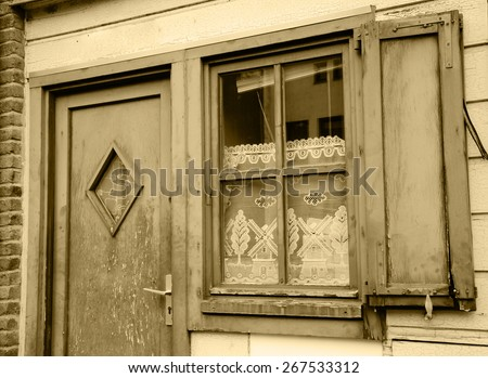 A front of the house. A door and a window with white lace curtain decorated with windmill and tree pattern and wooden hinged shutters . (Amiens, Picardy, France)  Rustic background. Aged photo. Sepia. - stock photo