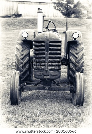 A front view of an old farm tractor sitting in a field.  Lightly toned Black and White for an aged vintage look.  - stock photo