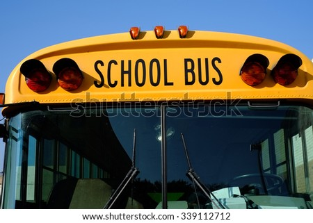 A frontal view of the iconic yellow school bus which many children still rely on  for transportation.  - stock photo