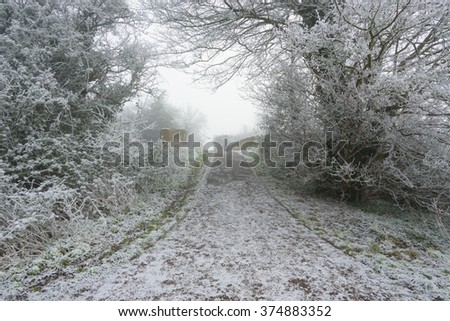 A frost covered footpath going over a canal bridge on a cold and foggy winters day. - stock photo