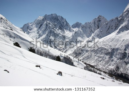 A frosty and sunny day is in mountains. Ski slopes