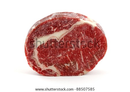 A frozen cut of outer side of the rib, prime rib eye steak on a white background - stock photo