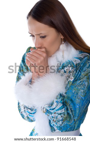 A frozen girl in a suit Maiden warms his hands with his breath - stock photo