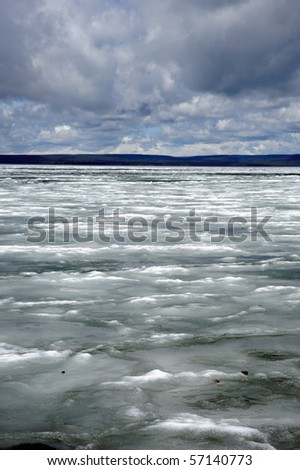 A frozen lake with dramatic cloudy sky