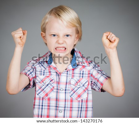 A frustrated and angry looking young boy with fists clenched and pulling a face. Isolated on white. - stock photo