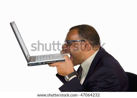 a frustrated and angry mature African-American businessman biting into his laptop, isolated on white background - stock photo