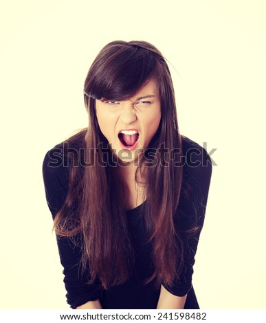 A frustrated and angry woman is screaming out loud. - stock photo