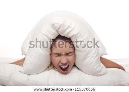 A frustrated woman is screaming as she is holding a pillow over her head. Screaming woman.