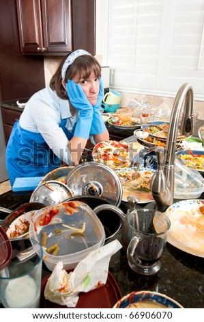 A frustrated woman prepares to wash a large set of dirty dishes.