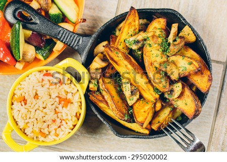 A frying pan of baked potatos with a bowl of rice and vegetables - stock photo