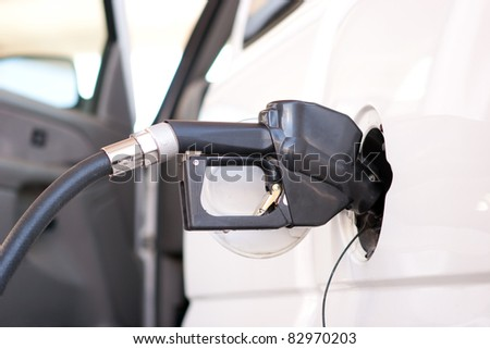 A fuel pump nozzle inserted into a vehicle's gas door - stock photo