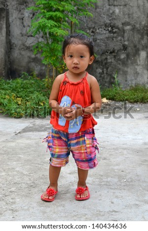 A full body portrait of beautiful Asian little girl with innocent eyes