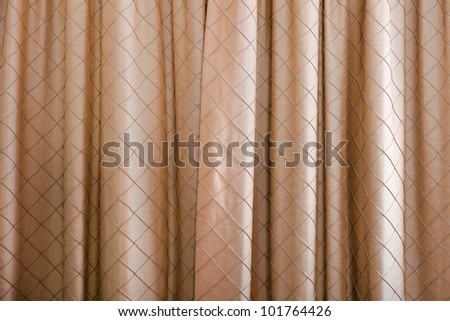 A full frame background of some closed brown curtains with a diamond pattern.