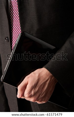 A full frame shot of a businessman holding a black laptop computer under his arm.  Suit and tie act as background.  Copyspace at the top and on the laptop. - stock photo