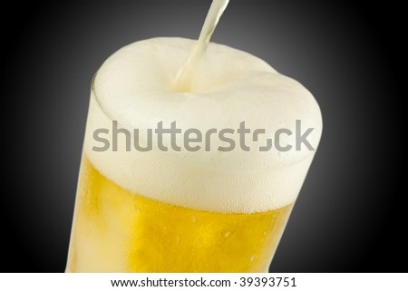 A full glass of beer being poured - stock photo